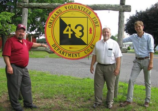 "The three County Commission Members standing around a sign which reads, ""Orleans Volunteer Fire D"